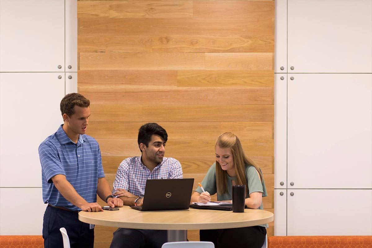 Students talk around a computer